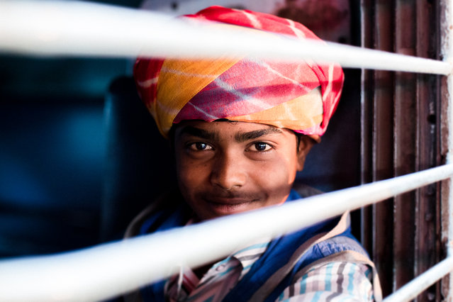 """Train Journey"". A young man in early morning light waiting for the train to leave. Photo location: Jodhpur Train Station, India. (Photo and caption by Laura Simonsen/National Geographic Photo Contest)"