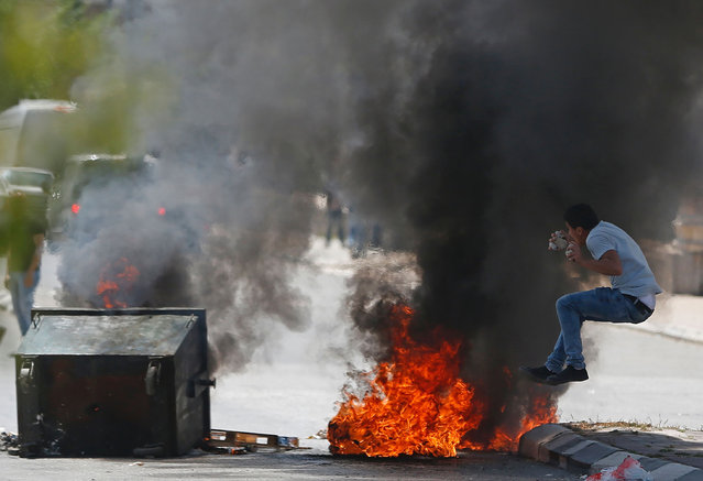 A Palestinian protester jumps near burning tyres during clashes with Israeli security forces following a demonstration in the West Bank town of Bethlehem to show their support for Palestinians imprisoned in Israeli jails after hundreds of detainees launched a hunger strike on April 17, 2017. More than 1,000 Palestinians in Israeli jails launched a hunger strike following a call from Palestinian leader and prominent prisoner Marwan Barghouti, a Palestinian Authority official said. (Photo by Ahmad Gharabli/AFP Photo)