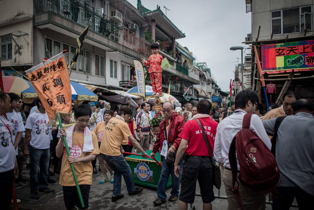 "A child is paraded on a float during the ""Bun Festival"" on the island of Cheung Chau in Hong Kong on May 6, 2014. The traditional ""Bun Festival"" is held every year to placate the hungry ghosts of old pirates. Legend has it that buns bring good luck to the island's fisherman protecting them from the spirits of pirates that once lurked in the region. (Photo by Philippe Lopez/AFP Photo)"