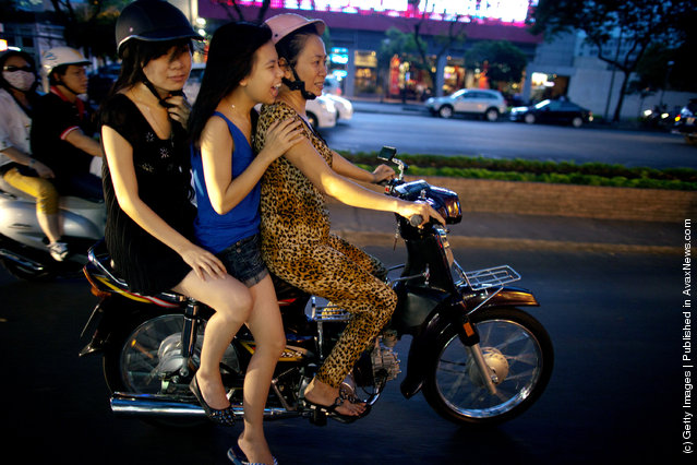 Vietnamese women cruise down the street on a motorcycle