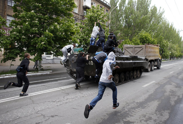 Children run to climb on a broken armoured vehicle of Ukrainian forces as is taken away by pro-Russian militants in Mariupol May 9, 2014. Ukrainian security forces killed about 20 pro-Russian rebels who tried to seize control of police headquarters in the eastern port city of Mariupol on Friday, the Interior Minister said. (Photo by Marko Djurica/Reuters)
