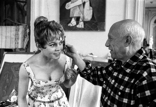 Spanish painter Pablo Picasso checks French actress Brigitte Bardot's face with a light meter at his studio in Vallauris, on the Cote d'Azur, during the Cannes Film Festival, April 1956, in France. Actors, directors and artists use the festival to showcase their films from across all genres, including documentaries. (Photo by Jerome Brierre/RDA/Getty Images)