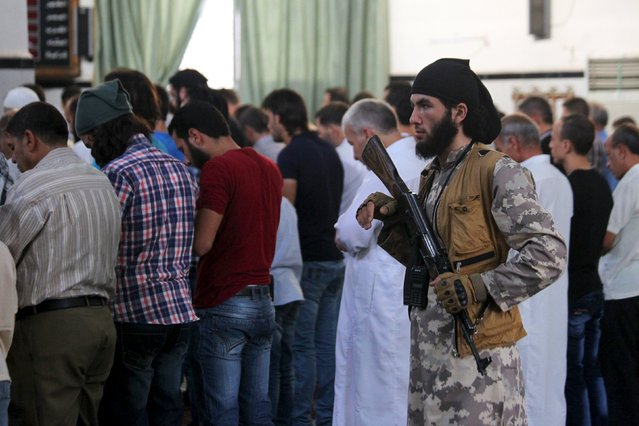 A rebel fighter carrying his weapon stands guard as men attend morning prayers on the first day of the Muslim holiday of Eid al-Fitr, which marks the end of the holy month of Ramadan, in the northwestern city of Ariha, in Idlib province, Syria, July 17, 2015. (Photo by Ammar Abdullah/Reuters)