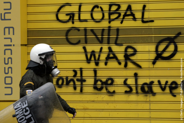 A policeman walks past graffiti that says 'Global civil war, don't be slaves' during a demonstration involving thousands of civilians on February 10, 2012 in Athens, Greece