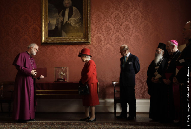 Britain's Queen Elizabeth II is shown the Ampulla and Coronation Spoon, which was used at her Coronation in 1953, by the Archbishop of Canterbury Rowan Williams as her husband Prince Philip, Duke of Edinburgh, and other Christian guests watch, during a multi-faith reception at Lambeth Palace