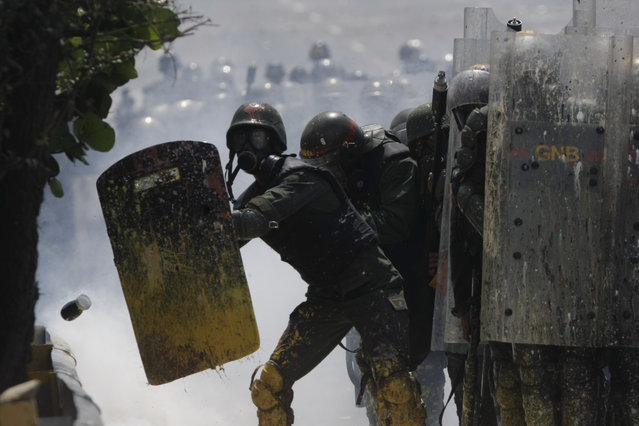 Bolivarian National Guards shield themselves from a jar of fecal matter flying at them, thrown by anti-government protesters in Caracas, Venezuela, Wednesday, May 10, 2017. (Photo by Fernando Llano/AP Photo)
