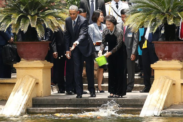 U.S. President Barack Obama (L) and Vietnam's National Assembly Chairwoman Nguyen Thi Kim Ngan feed fish in a pond, in the gardens of the presidential palace in Hanoi, Vietnam May 23, 2016. (Photo by Carlos Barria/Reuters)