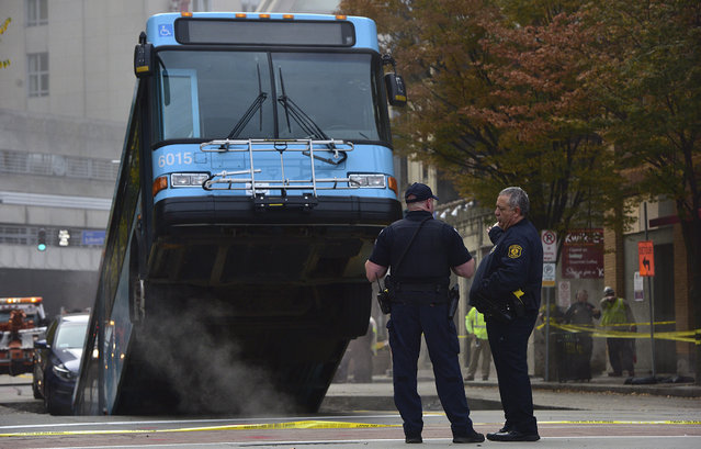 Pittsburgh police officers stand near a Port Authority bus that had fallen into a sinkhole along 10th Street and Penn Avenue in  Pittsburgh on Monday, October 28, 2019. The bus and a car fell in the sinkhole shortly before 8 a.m. One person was taken to the hospital for a minor injury. (Photo by Kristina Serafini/Pittsburgh Tribune-Review via AP Photo)