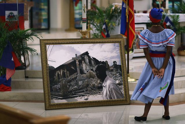 A dancer takes part in a dance near a framed picture of  a church that was destroyed by the massive 2010 Earthquake in Haiti during a service at the Notre Dame D'Haiti Catholic Church as they celebrate Haitian Flag day in the Little Haiti neighborhood on May 18, 2017 in Miami, Florida. The prayer service also touched on the church's concern about the outcome of the decision on extending the Temporary Protected Status for Haitians living in the United States because it would possibly mean friends and families would be sent back to Haiti. 50,000 Haitians have been eligible for TPS and now the Trump Administration has until May 23 to make a decision on extending TPS for Haitians or allowing it to expire on July 22. (Photo by Joe Raedle/Getty Images)