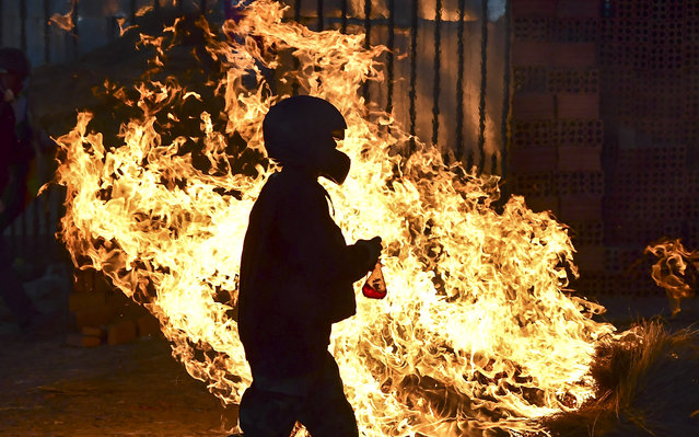 A man walks in front a fire blockade set by supporters of Bolivian ex-President Evo Morales in the outskirts of Sacaba, Chapare province, Cochabamba, on November 18, 2019. Bolivia's interim president said Sunday she will call new elections soon, as the country struggles with violent unrest a week after the resignation of Evo Morales. (Photo by Ronaldo Schemidt/AFP Photo)