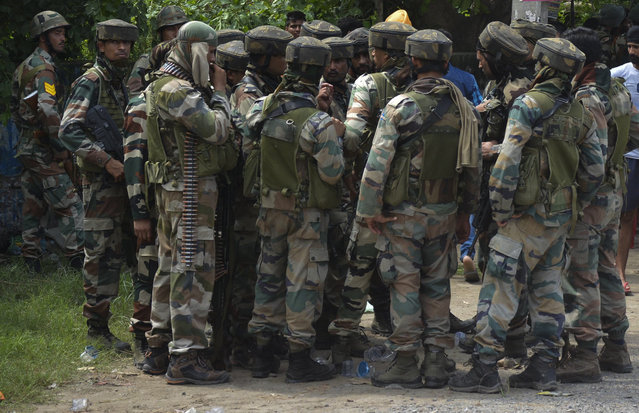 Indian army listen instructions from a higher commander during a fight in the town of Dinanaga, in the northern state of Punjab, India, Monday, July 27, 2015. Indian army commandos joined police in fighting suspected militants who fired at a bus station and stormed into police barracks on the outskirts of a northern town bordering Pakistan early Monday. Rebels have been fighting for an independent Kashmir or its merger with Pakistan since 1989. (Photo by Prabhjot Gill/AP Photo)