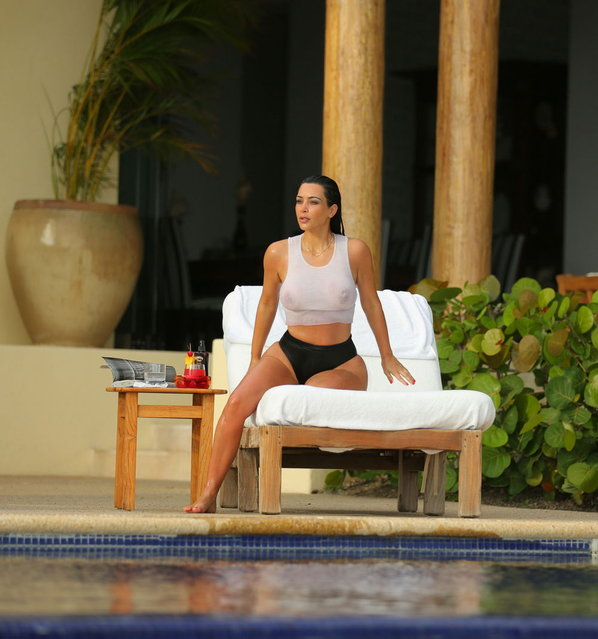 Kim Kardashian looks stunning in a see-through white tank top as she enjoys a second honeymoon in Mexico with Kanye West. The newly-weds stayed at the exclusive home of Girls Gone Wild founder Joe Francis, after jetting in to Punta Mita, to catch some pool side relaxation. The Wests honeymooned in Ireland and Prague after their May 24 wedding in Italy. (Photo by Brian Prahl/Splash News)