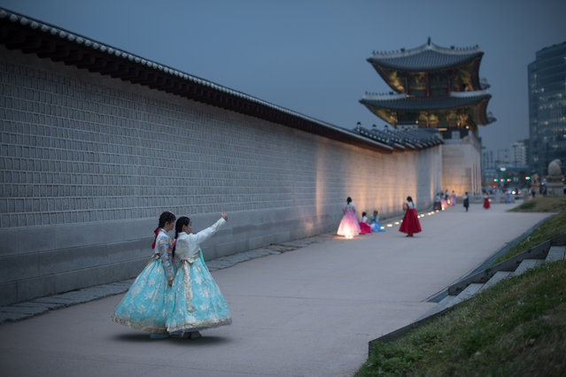 People wearing traditional Korean hanbok dress pose for photos as they visit Gyeongbokgung palace in central Seoul on November 4, 2016. (Photo by Ed Jones/AFP Photo)