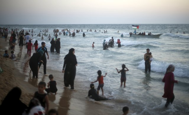 Palestinians enjoy the warm weather on a beach along the Mediterranean Sea in the northern Gaza Strip July 24, 2015. (Photo by Mohammed Salem/Reuters)