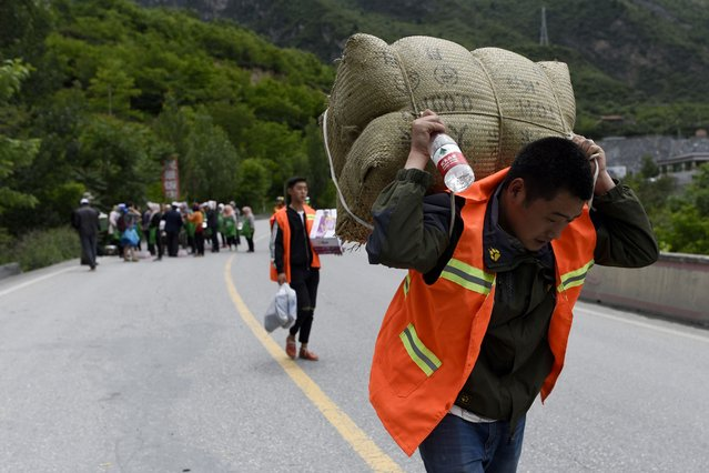 A man carries relief supplies as he heads to a landslide area in the village of Xinmo in Maoxian county, China's Sichuan province on June 25, 2017. (Photo by Wang Zhao/AFP Photo)