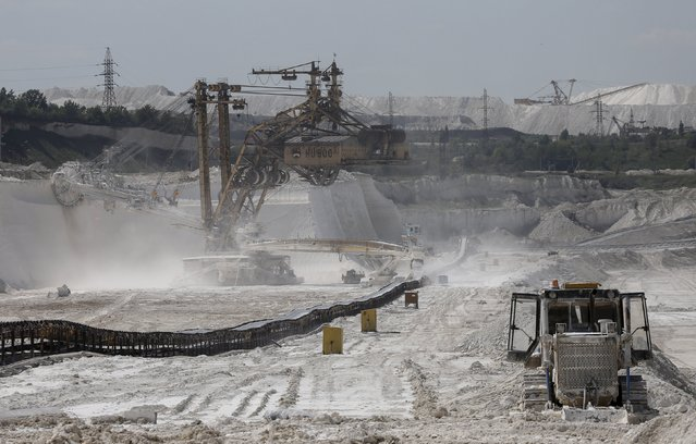 A rotary dredge (L) cuts the bedrock at an open-cast iron ore mine of the Stoilensky mining and concentration plant (GOK), owned by the Novolipetsk (NLMK) steel mill, in the city of Stary Oskol in Belgorod region, Russia, August 4, 2015. (Photo by Maxim Shemetov/Reuters)