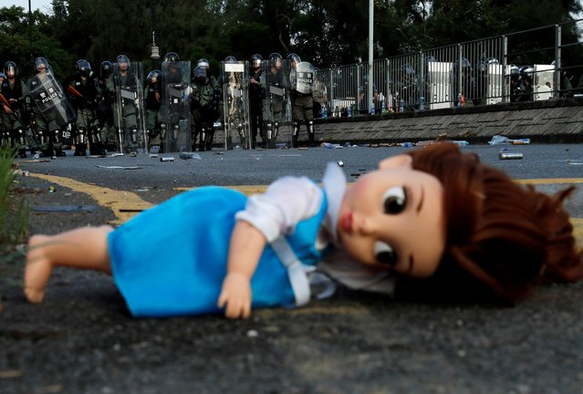 A doll left by the protesters lies on the ground as riot police officers block the street during a demonstration in support of the city-wide strike and to call for democratic reforms at Tai Po residential area in Hong Kong, China, August 5, 2019. (Photo by Tyrone Siu/Reuters)