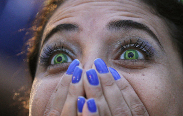 A Brazil soccer fan wearing contact lenses that mimic the Brazilian flag reacts as she watches her team play Germany in a World Cup semifinal game via live telecast inside the FIFA Fan Fest area on Copacabana beach in Rio de Janeiro, Brazil, Tuesday, July 8, 2014. (Photo by Leo Correa/AP Photo)