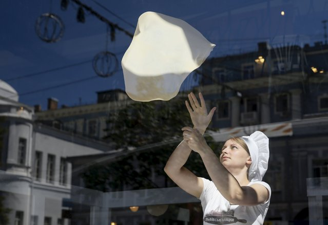 A woman prepares dough for a strudel at a cafe in central Kiev, Ukraine, August 7, 2015. (Photo by Valentyn Ogirenko/Reuters)
