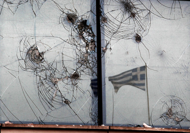 A Greek flag is reflected on the smashed windows of a bank in Athens.