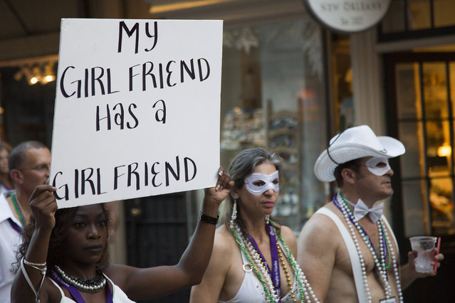 """A provocative sign is displayed during the Sexual Freedom Parade, part of Naughty in N'awlins held in New Orleans, Louisiana, Wednesday July 5th, 2017. These are the photos from inside the world's largest swinging convention for couples. The exclusive images reveal the unlikely couples who like to engage in sexual relations with other people besides their partners –  and show that swinging is more 'normal' than you think. Over 1,000 couples attend """"Naughty in N'awlins"""" in New Orleans, USA every year. The week-long convention consists of seminars, workshops, naked speed dating events, nightly erotic theme balls and a groundbreaking Sexual Freedom Parade. The Parade brings awareness to polyamorous relationships, archaic laws outlawing s*x toys as well as couples in the swinging lifestyle. (Photo by Mathew Growcoot/News Dog Media)"""