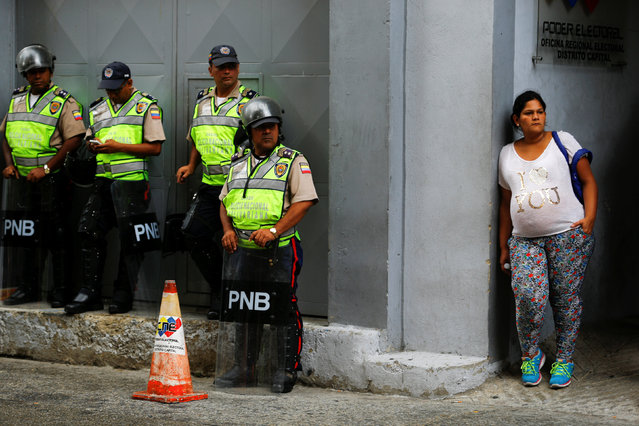 A pregnant woman stands next to riot police officers outside a validation center during Venezuela's National Electoral Council (CNE) second phase of verifying signatures for a recall referendum against President Nicolas Maduro in Caracas, Venezuela June 20, 2016. (Photo by Ivan Alvarado/Reuters)