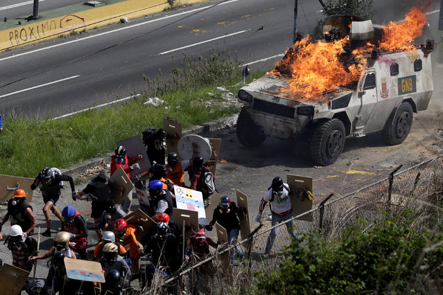 An armored vehicle is seen lit on fire during clashes with demonstrators at a rally against Venezuelan President Nicolas Maduro's government in Caracas, Venezuela, July 18, 2017. (Photo by Marco Bello/Reuters)