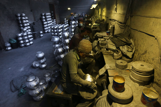 Afghan labors work on cooking pots made out of aluminum at a factory, on the outskirts of Kabul, Afghanistan, Tuesday, August 4, 2015. Men working at the factory earn an average of 600 AFN ($ 9.83 cents) per day. (Photo by Rahmat Gul/AP Photo)