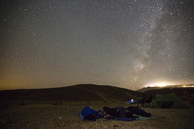 People sleep under the sky in the early morning during the Perseid meteor shower in Ramon Carter near the town of Mitzpe Ramon, southern Israel, August 13, 2015. (Photo by Amir Cohen/Reuters)