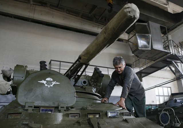 An employee repairs an armored vehicle at the Kiev armored plant, Ukraine, August 14, 2015. (Photo by Valentyn Ogirenko/Reuters)