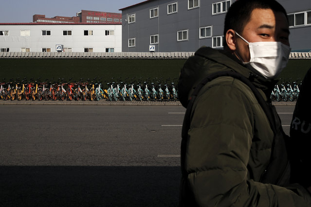 A man wearing a mask stands near a pile of bicycles from bike-sharing companies parked outside a subway station in Beijing, Monday, February 10, 2020. (Photo by Andy Wong/AP Photo)