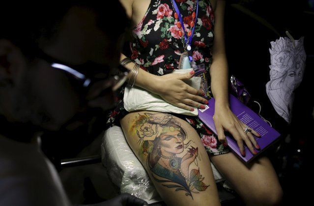 A woman sits as she gets a tattoo on her leg during the annual Panama City Ink Fest in Panama City August 16, 2015. (Photo by Carlos Jasso/Reuters)