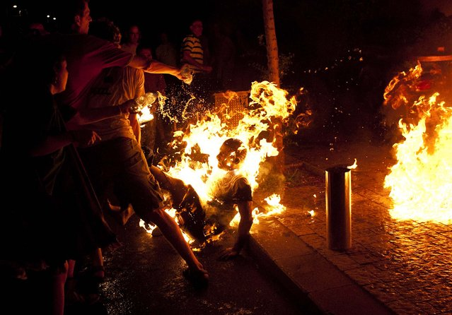 People try to extinguish flames after a man set himself on fire during a protest in Tel Aviv on July 14, 2012