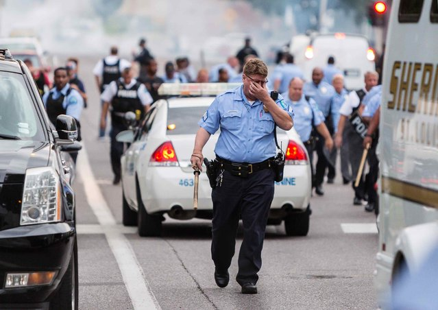 A policeman rubs his eyes after police attempted to disperse a crowd using what appeared to be teargas after a shooting incident in St. Louis, Missouri August 19, 2015. (Photo by Kenny Bahr/Reuters)
