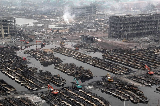 Rescuers cleaning up damaged cars during the explosions in Tianjin. Cyanide levels more than 350 times standard limits have been detected in water close to the site of deadly explosions in the Chinese port city of Tianjin, officials said on August 20, 2015. (Photo by AFP Photo)