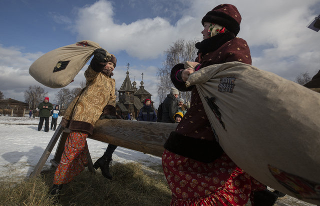 Girls play with fighting sacks on a bench during Maslenitsa celebrations in the town of Suzdal (200km from Moscow), Russia,  29 February 2020. The Maslenitsa festival, which originates from Slavic mythology, takes place this year from 24 February to 01 March. It is usually celebrated in the last week before the Great Lent. (Photo by Sergei Ilnitsky/EPA/EFE)