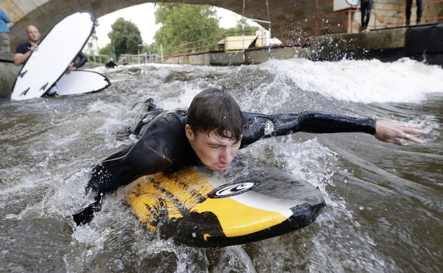 Tomas Sefrna swims to catch an artificial wave built on Elbe river's channel in Brandys nad Labem, Czech Republic, Tuesday, August 5, 2014. The recently opened wave serves as the only surf spot in the landlocked Czech Republic. (Photo by Petr David Josek/AP Photo)