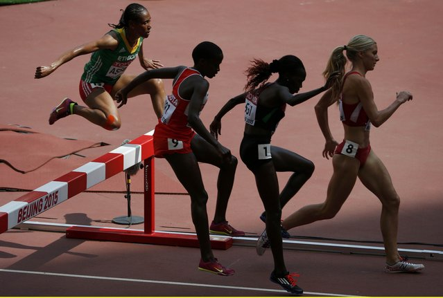 Athletes jump over a barrier in the women's 3000 metres steeplechase heats during the 15th IAAF World Championships at the National Stadium in Beijing, China August 24, 2015. (Photo by David Gray/Reuters)
