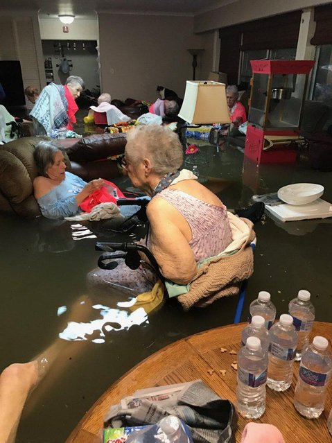 In this Sunday, August 27, 2017, photo provided by Trudy Lampson, residents of the La Vita Bella nursing home in Dickinson, Texas, sit in waist- deep flood waters caused by Hurricane Harvey. Authorities said all the residents were safely evacuated from the facility. (Photo by Trudy Lampson via AP Photo)