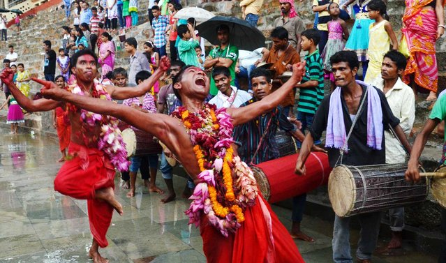 A Hindu priest, face smeared with color and sacrificial blood, heads towards a goat sacrifice during the Deodhani festival at the Kamakhya Hindu temple on August 18, 2015 in Guwahati, India. The Deodhani festival is a 5 day long event to celebrate and worship the Serpent Goddess, Maa Manasa at the Kamakhya temple. During this festival devotees present animal sacrifices. (Photo by Anuwar Ali Hazarika/Barcroft India)