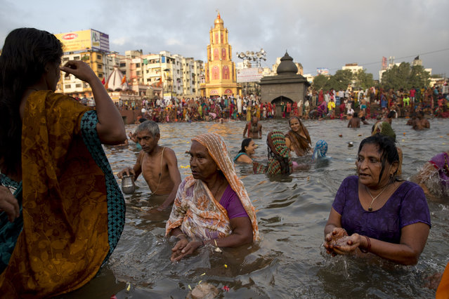 Indian devotees perform rituals as they take holy dips in the Godavari River during Kumbh Mela, or Pitcher Festival, in Nasik, India, Wednesday, August 26, 2015. (Photo by Tsering Topgyal/AP Photo)