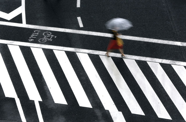 A woman walks on a pedestrian crossing in the rain Wednesday, June 21, 2017, in Tokyo. (Photo by Eugene Hoshiko/AP Photo)