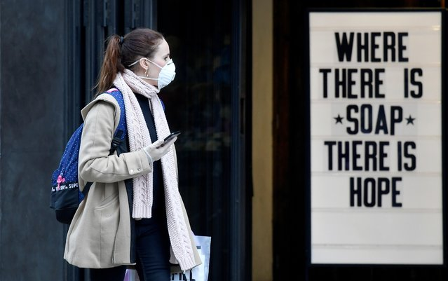A woman wearing a protective face mask walks past a shop, as the spread of the coronavirus disease (COVID-19) continues, in London, Britain, March 20, 2020. (Photo by Toby Melville/Reuters)
