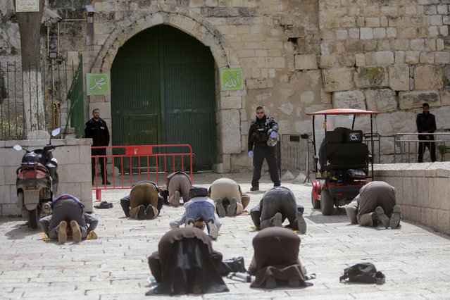 People pray in front of the shuttered gates to al-Aqsa mosque compound as all prayers are suspended to prevent the spread of coronavirus in Jerusalem, Monday, March 23, 2020. In Israel daily life has largely shut down with coronavirus cases multiplying greatly over the past week, (Photo by Mahmoud Illean/AP Photo)