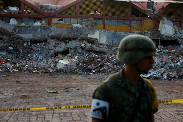 A soldier stands in front of the rubbles of a part of the municipal palace, after an earthquake struck the southern coast of Mexico late on Thursday, in Juchitan, Mexico, September 9, 2017. (Photo by Carlos Jasso/Reuters)