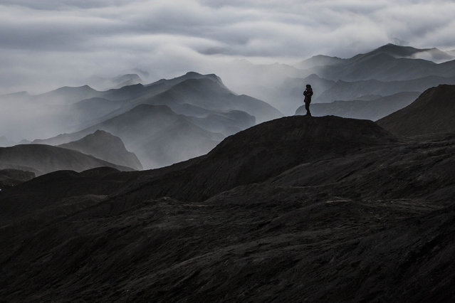 "A Tenggerese worshipper stands at Mount Bromo's ""Sea of Sand"" during the Yadnya Kasada Festival on August 12, 2014 in Probolinggo, East Java, Indonesia. (Photo by Ulet Ifansasti/Getty Images)"