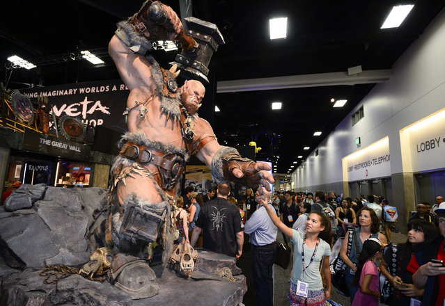 """A fan reaches out to touch the finger of a giant """"World of Warcraft"""" Orgrim statue in the exhibit hall on day two of Comic-Con International held at the San Diego Convention Center Friday, July 22, 2016, in San Diego.  (Photo by Denis Poroy/Invision/AP)"""