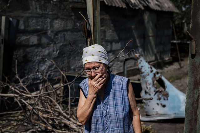 Galina, a local resident, cries in front of her house in the village of Olenivka, eastern Ukraine, south of the besieged rebel stronghold of Donetsk, on August 21, 2014. On the evening of August 18, shelling from Grad multiple rocket launchers destroyed and damaged some 30 houses in Olenivka, killed a woman and injured two. Pro-Russian rebels and government troops mutually accuse each other of being respinsible for the shelling. (Photo by Dimitar Dilkoff/AFP Photo)