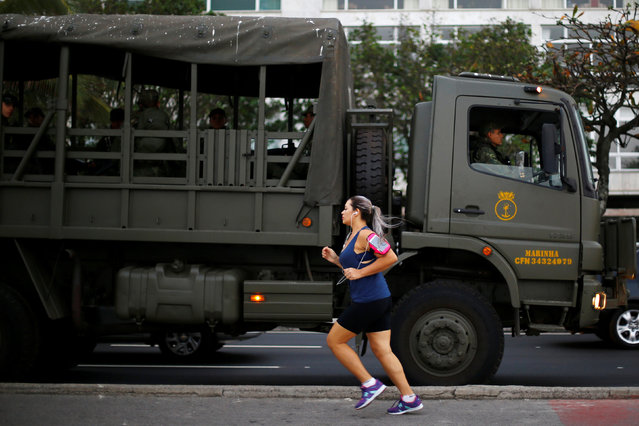 A woman runs past a Brazilian soldiers' vehicle as they patrol along Ipanema Beach, ahead of the Rio 2016 Olympic Games, in Rio de Janeiro, Brazil July 25, 2016. (Photo by Ivan Alvarado/Reuters)