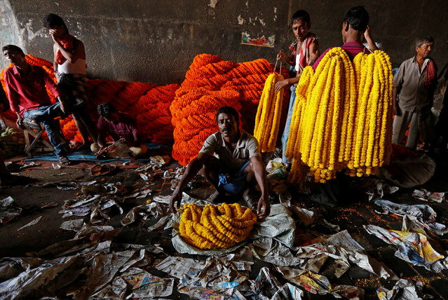 Vendors sell garlands, which are used to decorate temples and homes during the Hindu festival of Durga Puja, at a wholesale flower market in Kolkata, India September 26, 2017. (Photo by Rupak De Chowdhuri/Reuters)